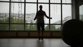 El hombre muscular que hace salto de la cuerda se resuelve en el gimnasio - silueta, cámara lenta - tiro del resbalador metrajes
