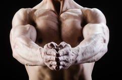 El hombre muscular que presenta en estudio oscuro fotos de archivo