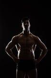 El hombre muscular que presenta en estudio oscuro imagen de archivo libre de regalías