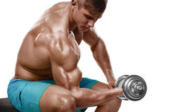 El hombre muscular que resuelve hacer ejercita con pesas de gimnasia en los bíceps, torso desnudo masculino fuerte, aislado sobre Imagen de archivo