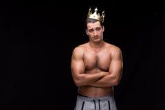 El hombre muscular rasgado con la corona del rey fotos de archivo libres de regalías