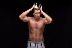 El hombre muscular rasgado con la corona del rey fotografía de archivo