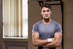 El hombre muscular rasgado en el gimnasio que hace deportes imagen de archivo