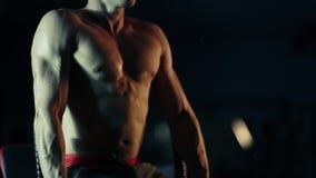 El hombre muscular realiza ejercicios en los músculos de la prensa en un gimnasio oscuro, levantando pesos metrajes