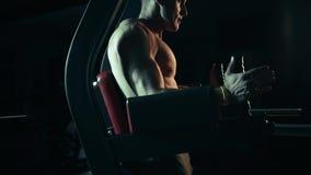 El hombre muscular realiza ejercicios en los músculos de la prensa en un gimnasio oscuro, levantando pesos almacen de video