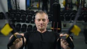 El hombre muscular se tira para arriba en las correas 4K MES lento de TRX almacen de video