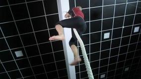 El hombre muscular sube la cuerda en el gimnasio metrajes