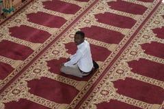 El hombre musulmán africano está rogando en la mezquita Fotografía de archivo