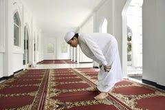 El hombre musulmán asiático joven está rogando a dios fotos de archivo libres de regalías