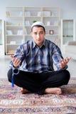 El hombre musulmán que ruega en casa Foto de archivo libre de regalías