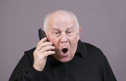 El hombre muy emocional con el microteléfono de teléfono grita en un fondo gris Imagenes de archivo