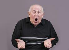 El hombre muy emocional gesticula las manos en un fondo gris Imagen de archivo