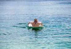 El hombre nada en el estilo del delfín del mar. Retrato en un día soleado Foto de archivo