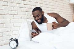 El hombre negro, despertado bebe el café en cama que hojea foto de archivo