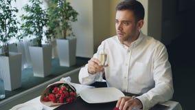 El hombre nervioso se está sentando solamente en la tabla en el restaurante, champán de consumición y está esperando a su novia,  metrajes