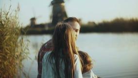 El hombre, el niño pequeño y la muchacha se sientan cerca de un lago de la puesta del sol El padre con dos niños disfruta del tie metrajes