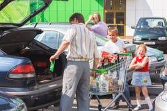 El hombre no identificado lleva hacia fuera mercancías del carro de la compra la parte posterior del th Imagen de archivo