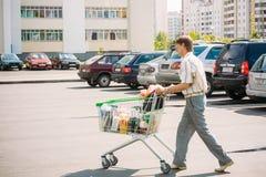 El hombre no identificado rueda el carro de la compra en el estacionamiento Fotografía de archivo libre de regalías