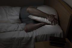 El hombre no puede dormir en la noche Foto de archivo