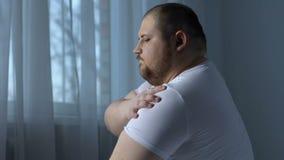 El hombre obeso perezoso que ejercita el hombro muscles, el desorden de la reumatología, falta de deporte almacen de metraje de vídeo