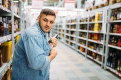 El hombre oculta la botella de alcohol debajo de su camisa foto de archivo libre de regalías