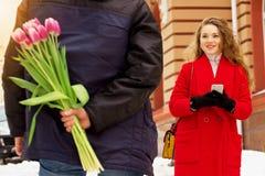 El hombre oculta las flores detrás el suyo detrás para su novia Pares jovenes hermosos que caminan junto a través de las calles d Fotos de archivo libres de regalías
