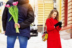El hombre oculta las flores detrás el suyo detrás para su novia Pares jovenes hermosos que caminan junto a través de las calles d Foto de archivo