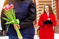 El hombre oculta las flores detrás el suyo detrás para su novia Pares jovenes hermosos que caminan junto a través de las calles d Fotografía de archivo
