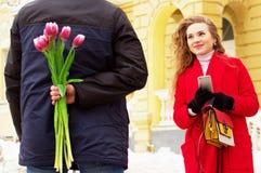 El hombre oculta las flores detrás el suyo detrás para su novia Pares jovenes hermosos que caminan junto a través de las calles d fotografía de archivo libre de regalías