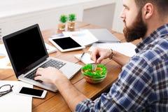 El hombre ocupado almuerza el almuerzo de negocios en interior moderno de la oficina fotografía de archivo