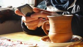 El hombre ocupado con un teléfono móvil bebe el café en el café étnico almacen de video