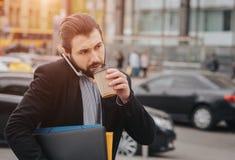 El hombre ocupado tiene prisa, él no tiene tiempo, él va a comer el bocado en camino Trabajador que come, café de consumición fotografía de archivo