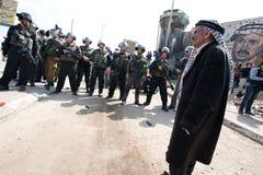 El hombre palestino enfrenta a soldados israelíes Imagenes de archivo