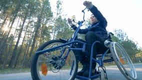 El hombre parapléjico está entrenando a sus brazos moviendo una silla de ruedas del entrenamiento 4K metrajes