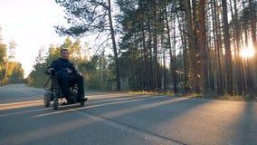 El hombre parapléjico se está moviendo a lo largo del camino en su silla de ruedas accionada en el bosque metrajes