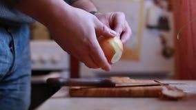 El hombre pela la cocina de las cebollas en casa almacen de video
