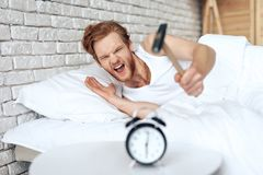 El hombre pelirrojo joven martilla el despertador imagen de archivo libre de regalías