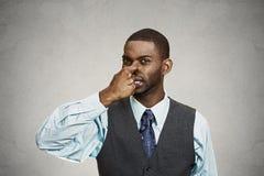 El hombre pellizca su nariz, olor muy malo, olor foto de archivo