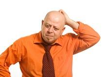 El hombre pensativo en una camisa anaranjada Imágenes de archivo libres de regalías