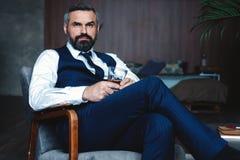 El hombre pensativo hermoso está tocando su barba, está mirando lejos y está pensando mientras que se sienta en butaca dentro foto de archivo libre de regalías