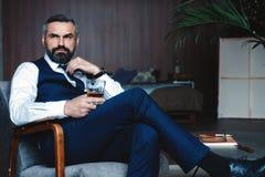 El hombre pensativo hermoso está tocando su barba, está mirando lejos y está pensando mientras que se sienta en butaca dentro fotos de archivo libres de regalías