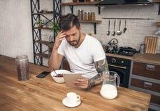 El hombre pensativo hermoso joven está teniendo sus cereales de desayuno con leche en la cocina y está leyendo noticias de la mañ fotos de archivo