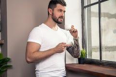 El hombre pensativo hermoso joven est? mirando la ventana y est? teniendo su caf? de la ma?ana fotos de archivo