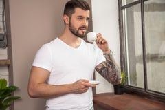 El hombre pensativo hermoso joven est? mirando la ventana y est? teniendo su caf? de la ma?ana foto de archivo libre de regalías
