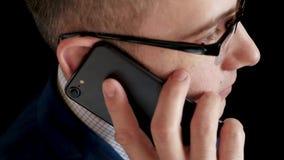 El hombre pensativo serio en un traje de negocios trae el teléfono a su oído y hace una llamada El hablar que habla del hombre de almacen de video