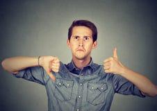 El hombre perplejo con los pulgares abajo manosea con los dedos encima de gesto Imagen de archivo