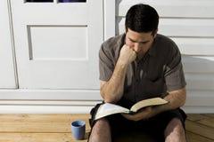 El hombre piensa mientras que él lee la biblia Imagenes de archivo