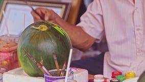 El hombre pinta la sandía con el cepillo para el mercado de TET en Vietnam almacen de video
