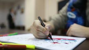 El hombre pinta las páginas de la caja de colorante