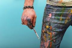 El hombre pintado con los cepillos foto de archivo